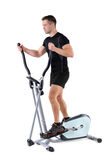 Young man doing exercises on elliptical trainer Royalty Free Stock Photo