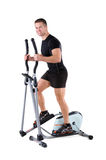 Young man doing exercises on elliptical trainer Royalty Free Stock Photos