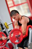 Young man doing exercises in the gym Royalty Free Stock Photo