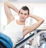 Young man doing exercises at gym Stock Images