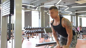 Young man doing exercises in a gym, workout.  stock footage