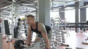Young man doing exercises in a gym, workout.  stock video footage