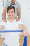 Young man doing exercises with the help of therapist Stock Image