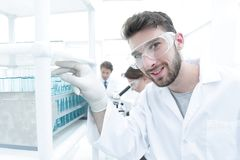 A young man doing an experiment in a chemical laboratory. Side view of young scientist in eyeglasses looking at test tube in research laboratory stock photo