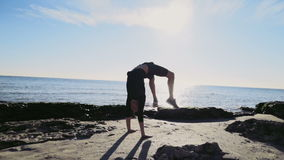 Young man doing gymnastics on the beach slow motion stock video footage