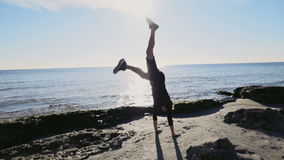 Young man doing gymnastics on the beach slow motion stock video