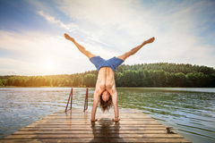 Young man doing a handstand on a wooden jetty stock photos