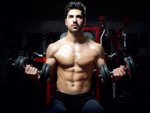 Young man doing heavy weight exercise in gym. Royalty Free Stock Photos