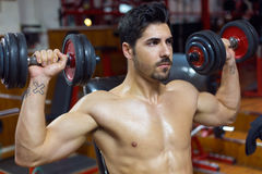 Young man doing heavy weight exercise in gym. Royalty Free Stock Image