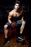Young man doing heavy weight exercise in gym. Royalty Free Stock Images