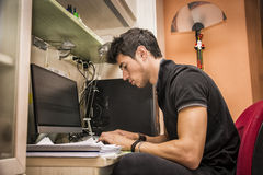 Young Man with Doing Homework at Computer Desk Royalty Free Stock Images