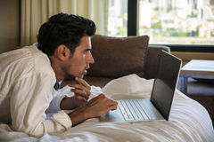Young Man Doing Homework on Laptop in Bedroom Royalty Free Stock Images