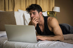 Young Man Doing Homework on Laptop in Bedroom Stock Photo