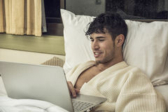 Young Man Doing Homework on Laptop in Bedroom Royalty Free Stock Photos