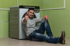 Young Man Doing Housework Laundry Thumbs Up Sign stock photography