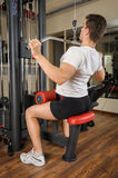 Young man doing lats pull-down workout in gym Stock Photography