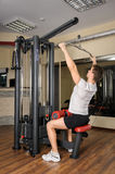 Young man doing lats pull-down workout in gym Royalty Free Stock Photos