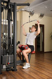 Young man doing lats pull-down workout in gym Stock Photo
