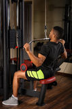 Young man doing lats pull-down workout. Handsome young african descent mixed race man doing lats pull-down workout in gym Stock Images