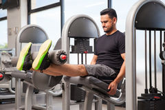 Young man doing leg extensions Royalty Free Stock Images