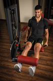 Young man doing legs extensions workout in gym Royalty Free Stock Image