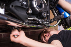 Young man doing maintenance on his motorbike Stock Photos