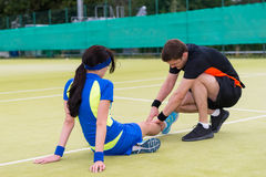 Young man doing massage to his female tennis partner. Young men doing massage to his female tennis partner after  tennis match on a court outdoor in summer or Royalty Free Stock Photography