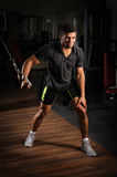 Young man doing one arm standing high cable fly. Handsome young african descent mixed race man doing one arm standing high cable fly workout in gym royalty free stock photos