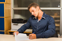 Young man doing paperwork at office desk, showing Royalty Free Stock Photography