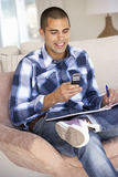 Young Man Doing Paperwork And Using Mobile Phone At Home Stock Photo
