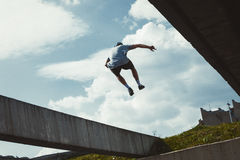 Young man doing parkour in the city. Young man doing parkour jump in urban space in the city  sunny spring summer day Royalty Free Stock Photo