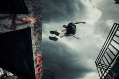 Young man doing parkour jump in the city royalty free stock photos