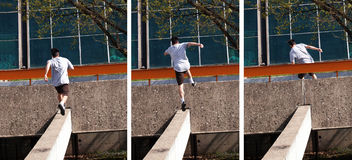 Young man doing parkour jump in the city stock image
