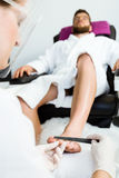 Young man doing pedicure in salon. Beauty concept. Royalty Free Stock Images