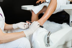 Young man doing pedicure in salon. Beauty concept. Royalty Free Stock Photo