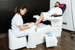 Young man doing pedicure in salon. Beauty concept. Stock Photography