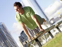 Young man doing press-ups on bench outdoors, smiling, low angle view (tilt) Royalty Free Stock Photos