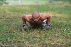 Young Man Doing Press Ups With Dumbbells Outdoors Stock Photography