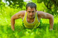 Young man doing press ups on the grass Stock Photos