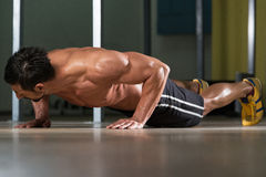 Young Man Doing Press Ups In Gym Stock Photography