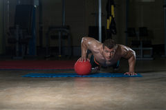 Young Man Doing Press Ups On Medicine Ball Royalty Free Stock Photos