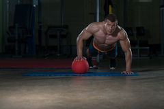 Young Man Doing Press Ups On Medicine Ball Stock Photography