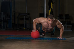 Young Man Doing Press Ups On Medicine Ball Royalty Free Stock Photography