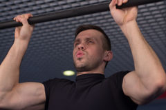A young man doing pull ups in the Gym Stock Images