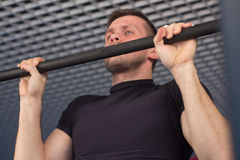 A young man doing pull ups in the Gym.  Stock Photo