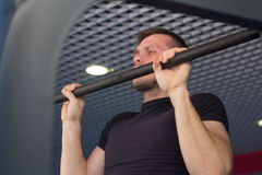 A young man doing pull ups in the Gym.  Stock Photos