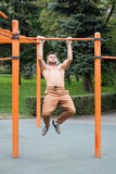 Young man doing pull ups on horizontal bar outdoors. Stock Images