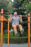 Young man doing pull ups on horizontal bar outdoors. Royalty Free Stock Image