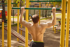Young man doing pull ups on horizontal bar outdoors Stock Images