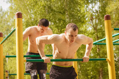 Young man doing pull ups on horizontal bar outdoors Royalty Free Stock Images